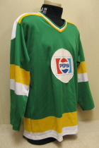 This green jersey with the Pepsi logo on it was used in the latter part of the 86-87 PeeWee A travel season. Worn by Cody Delperdang. The  white jerseys were a little more elaborate and they went through the season with only one set. The Team won the Midwest League tournament and advanced to the Central District Tier II tournament in St. Louis. Tournament rules dictated that two sets of jerseys so Dave Davies ordered the green ones and got the logo and numbers on them last minute. These were only wore those jerseys 2 games and  don't believe they were used for travel hockey next season.